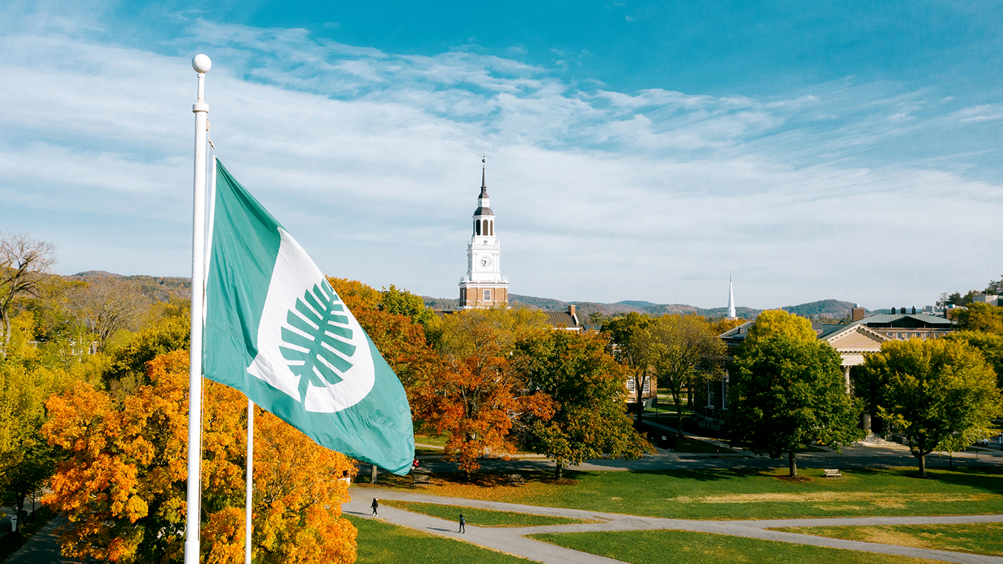 A photo of the Dartmouth flag in front of Baker Library in the fall
