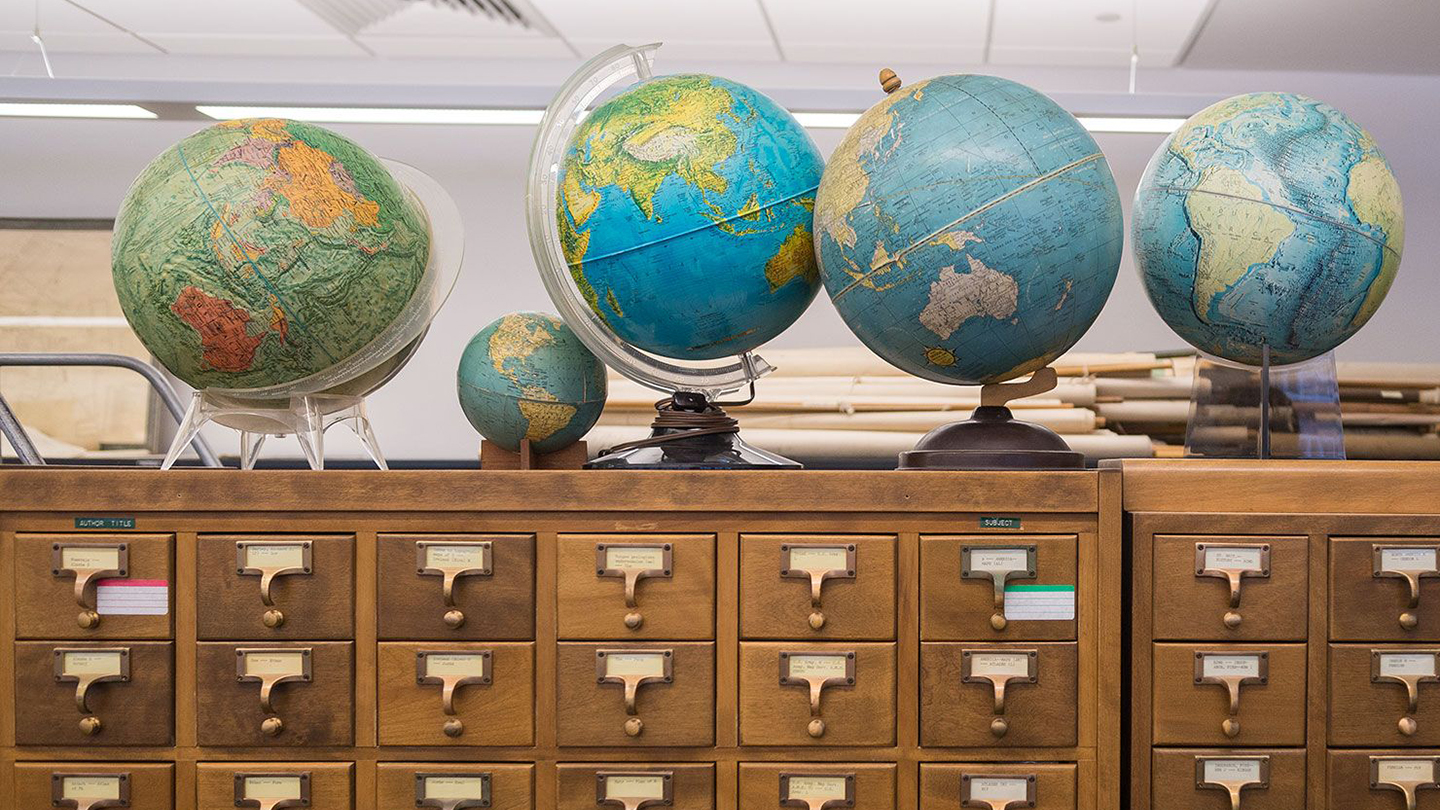 A photo of globes atop a library card catalog