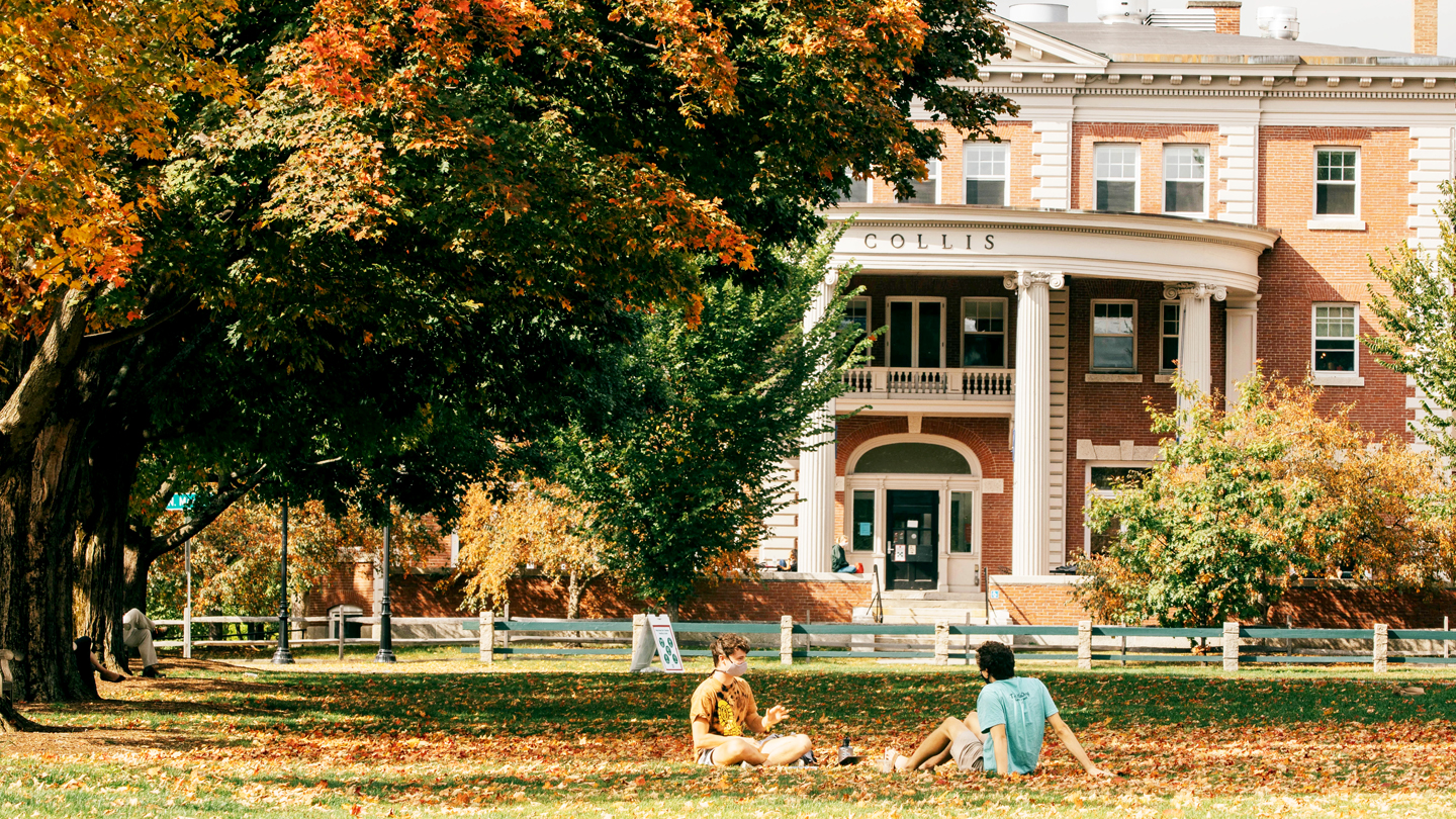 A photo of two students sitting on the Green amongst the fall leaves with Collis in the background