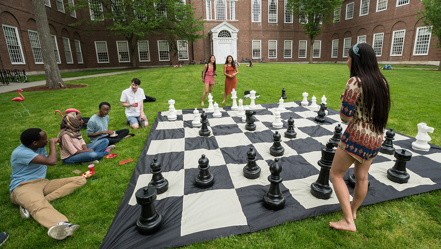 Photo of students playing on an over-sized chess board in front of Baker Library