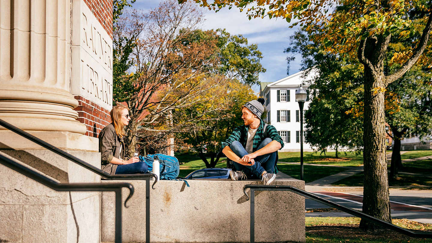A photo of students sitting outside of Rauner Library in the fall