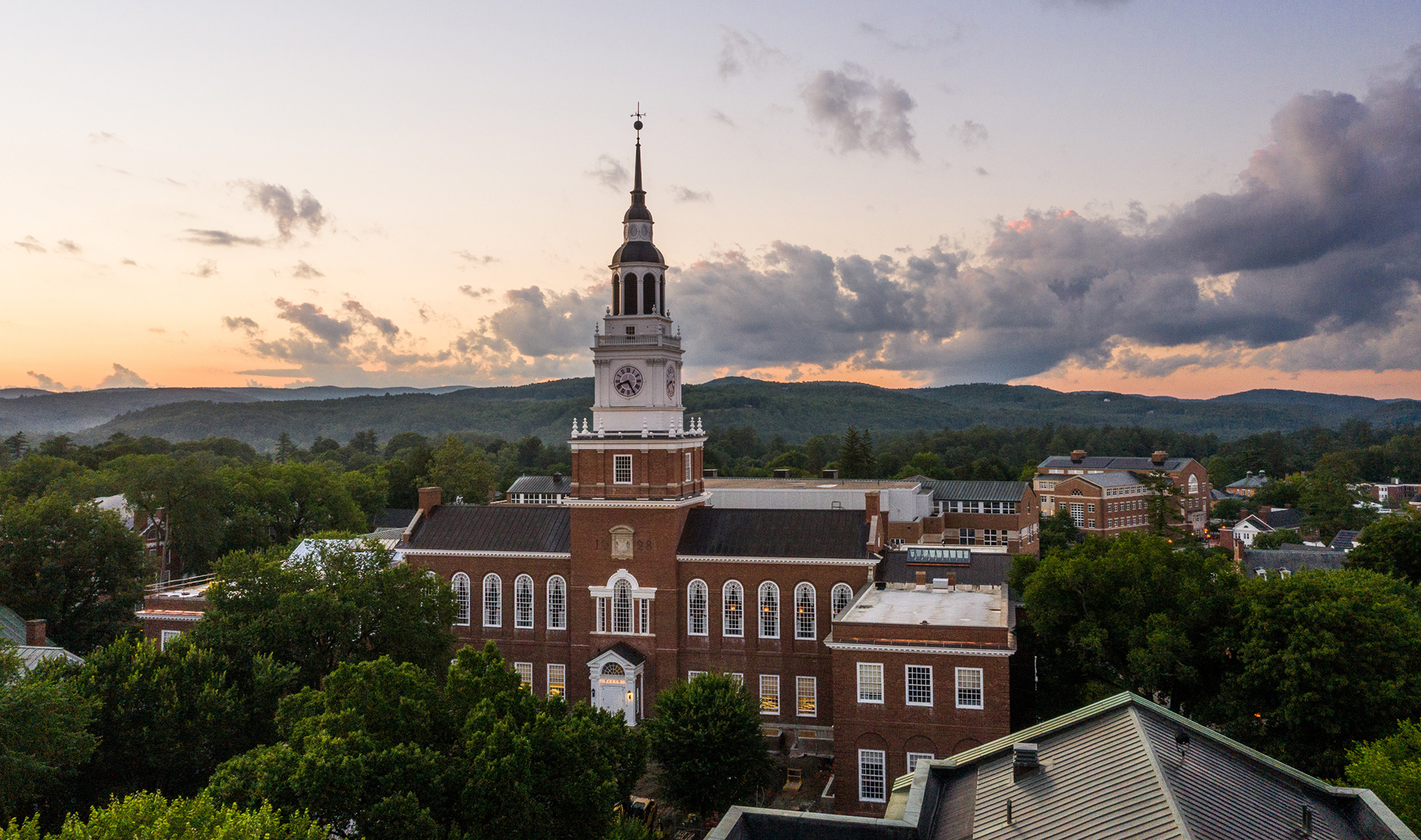 A photo of Baker Library with a sunset in the background