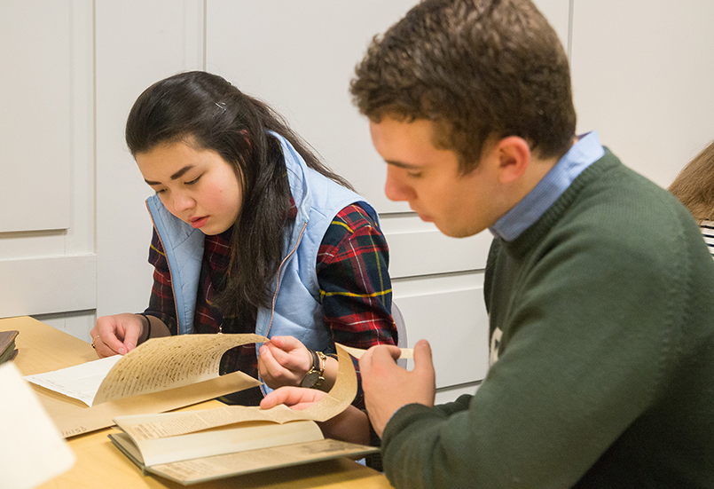 Photo of students looking at a book