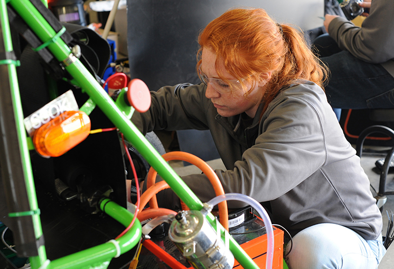 A photo of an engineering student working on Dartmouth's Formula One car