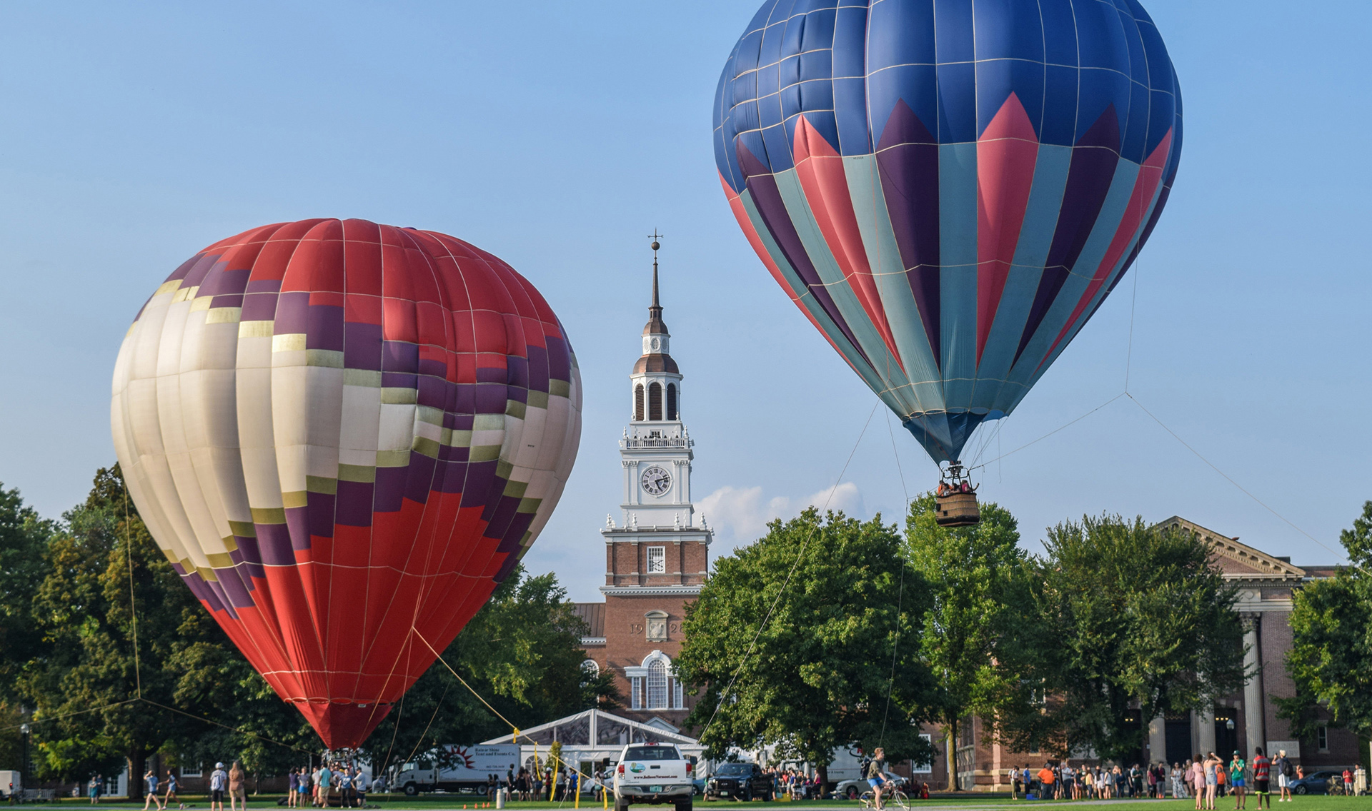 A photo of hot air balloons in front of Baker Library