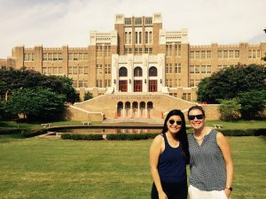 two women stand in front of historic school building