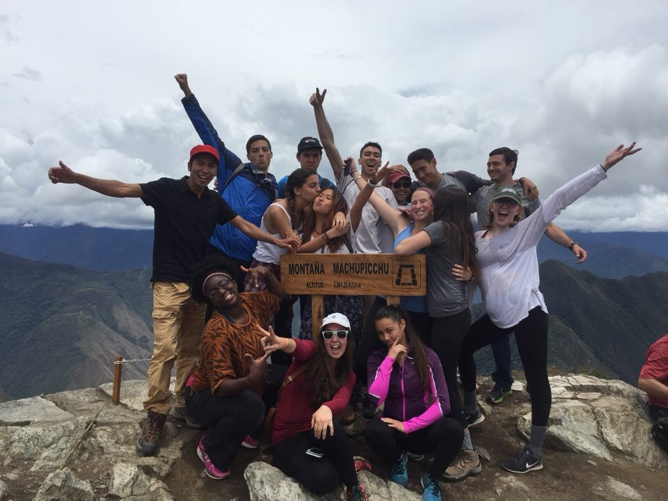 students posing with the Mt. Machu Picchu sign at the top of the mountain