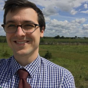 selfie of a young man with dark hair and glasses in front of a field