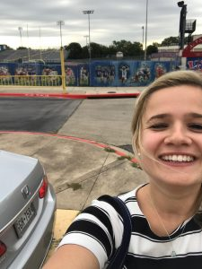 selfie of a young woman in front of a high school football stadium