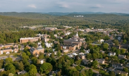 A photo of campus, taken by a drone, showing campus, surrounding buildings, and mountains in the distance, during the late spring