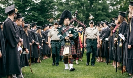 A photo of bagpiper Joshua Marks '96 leading a class to commencement