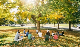 A photo of a class sitting on the lawn in fall
