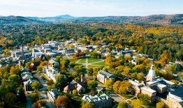 A photo of campus, taken by a drone, showing the Green, surrounding buildings, and mountains in the distance, during the fall