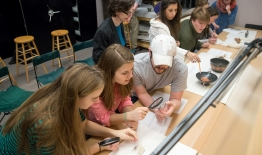 An image of students examining artifacts in a class