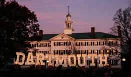 """A photo of marque letters spelling """"Dartmouth"""" in front of Dartmouth Hall at sunset"""