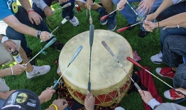 A photo of students sitting around a drum