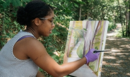 A photo of a student painting in nature