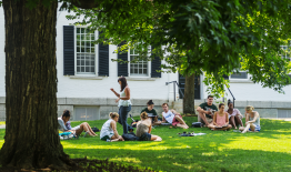 A photo of students sitting on the lawn of Dartmouth Hall in the summer