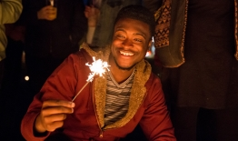 A photo of a smiling student holding a sparkler