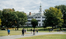 A photo of students crossing The Green with Dartmouth Hall in the distance
