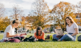 A photo of three female students studying on The Green