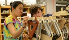 A photo of two students working on an engineering project