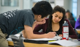 A photo of two students working on papers