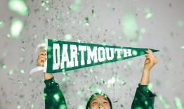 a photo of a student holding a Dartmouth pennant with glitter falling around her