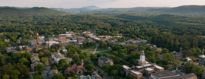 A photo of campus, taken by a drone, showing the Green, surrounding buildings, and mountains in the distance, during the summer