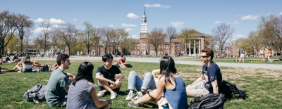 A photo of students sitting on the Green in small groups