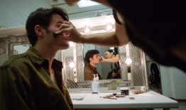 A photo of a student applying makeup to another student for a theatrical performance