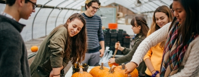 Photo of students carving pumpkins at the Organic Farm
