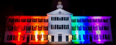 Photo of Dartmouth hall lit in the colors of the rainbow for Dartmouth PRIDE week