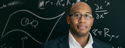 Photo of professor Devin Walker in front of a chalk board