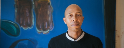 Photo of professor Enrico Riley standing in front of his painting