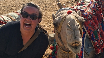 A photo of an admissions officer and a camel