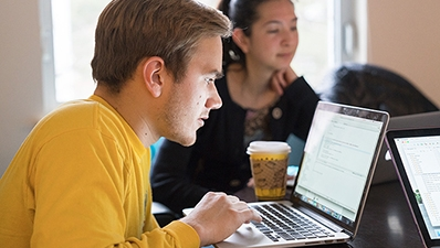 A photo of students looking at a laptop