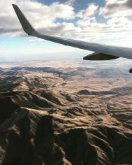 plane flying over rugged landscape
