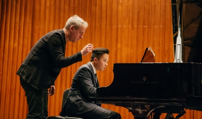 A photo of a student receiving instruction on the piano