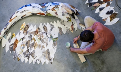 Photo of a student creating a sculpture out of cut paper