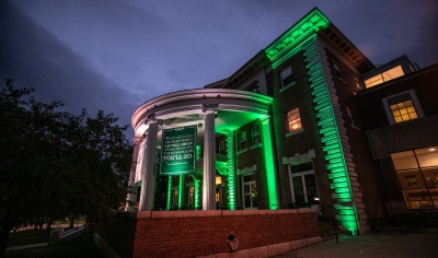 A photo of the front of Collis lit up with green lights at dusk.