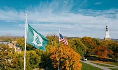 A photo of both the Dartmouth flag and the American flag fly over the Green in fall, with Baker Tower in the background