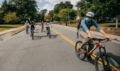 A photo of a group of students wearing masks and riding bikes.