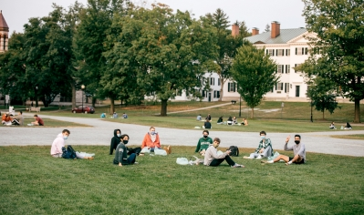 A photo of students with masks on sitting on the Green in large circles having conversations