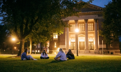An image of students sitting on the Green in front of Rauner wearing face masks