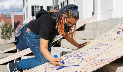 A photo of a student in a mask signing boards to be used in next year's Homecomming bonfire