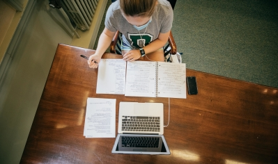 A photo of a student wearing a mask, studying in the library with written notes and a laptop
