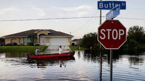 two people paddling a canoe up a flooded street in Florida