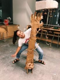 girl behind cardboard sculpture of a hand