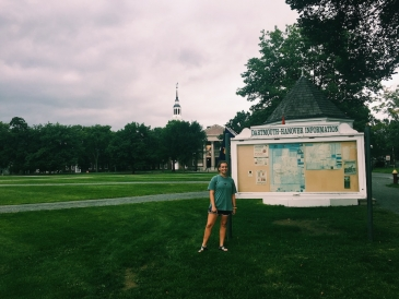 Abbi standing in front of a map on the green, with Baker Berry in the background